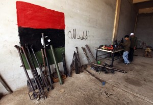 "Weapons warehouse: fighters during the revolution are repairing weapons taken from forces loyal to now-deposed leader Muammar Gaddafi.  Image Source: ""'It seems we are effectively arming Al Qaeda,' arms trafficking expert says,"" International Business Times, June 2011"
