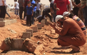 "Mourners by the graves of those killed in the 8 June anti-militia demonstrations in Benghazi. Source: ""No Impunity for 'Black Saturday' Benghazi Deaths: Investigate killings, clamp down on unlawful militias,"" Human Rights Watch Image from Reuters"