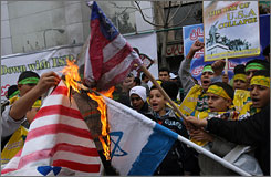 "Iranian students burn the U.S. flag in front of the former U.S. Embassy in Tehran, Iran, on 4 November in commemoration of the 1979 Iranian hostage crisis. Image source: ""Iranian Burn Flags, Cheer U.S. Embassy Takeover,"" USA Today"